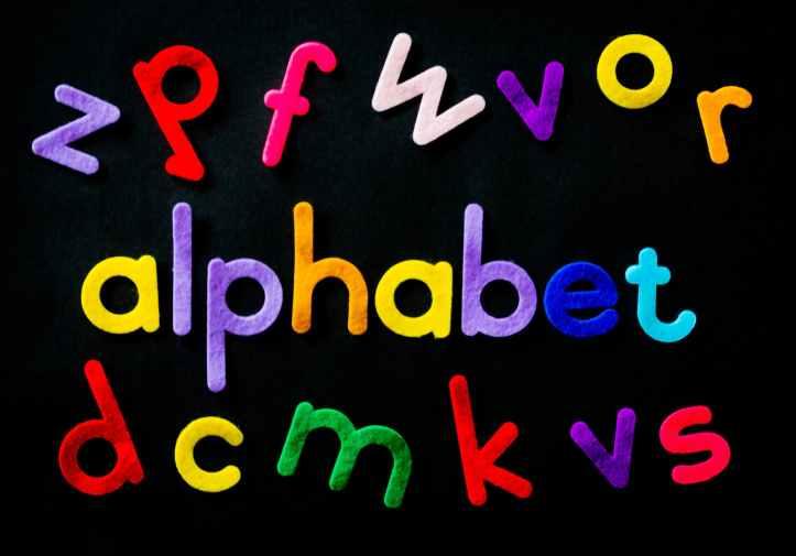 assorted color alphabet on black background