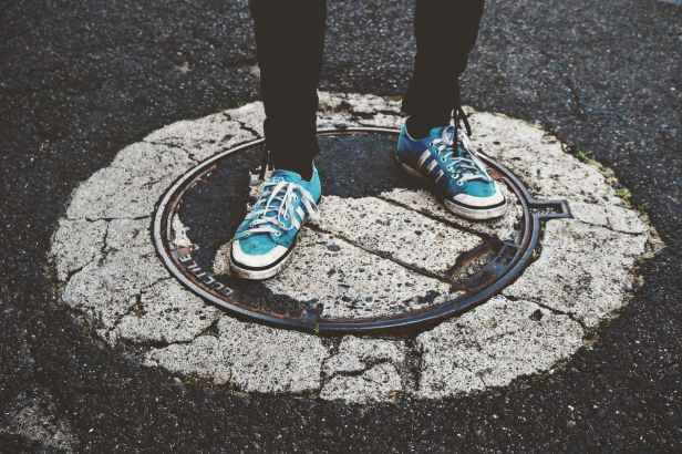 person standing on manhole cover
