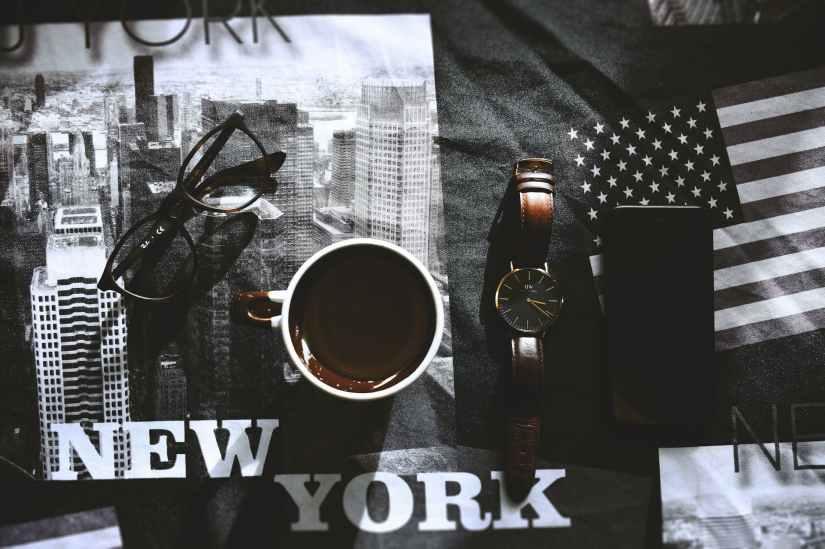 white and brown mug beside brown watch